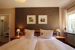 Blick über das Doppelbett der Ferienwohnung Lindenblüte mit dekorativer Rückwand hinterm Bett