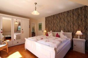 Doppelbett der Ferienwohnung Lindenblüte mit Fototapete an der Rückwand des Bettes