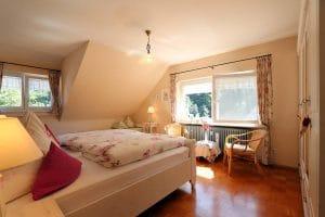 Doppelzimmer der Ferienwohnung Lindenblüte mit Blütenbettwäsche und weißen Möbeln