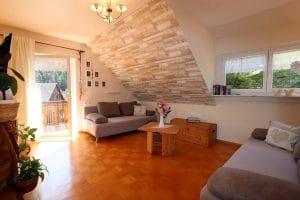 Wohnzimmer der Ferienwohnung Lindeblüte mit Couchgarnitur und Balkon
