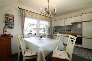Küche mit Esstisch und weißen Stühlen der Ferienwohnung Lindenblüte