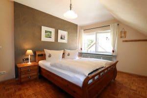 Doppelzimmer der Ferienwohnung Lindenblüte mit Parkettboden und dekorativer Rückwand hinterm Bett