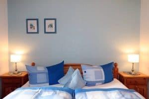 Doppelbett der Blauen Stube mit blauer Bettwäsche und blauer Rückwand hinterm Bett