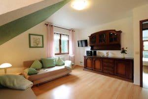 Wohnzimmer mit Couchecke unter der Dachschräge in der Ferienwohnung Tannenblick