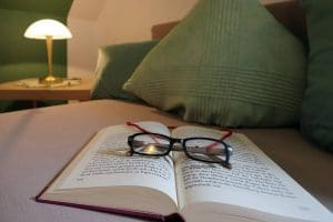 Buch mit Lesebrille auf der Couch im Wohnzimmer der Ferienwohnung Tannenblick