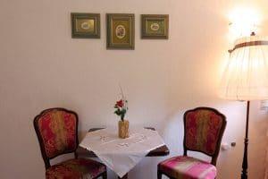Sitzplatz mit Tisch und 2 Stühlen im Wohnzimmer der Ferienwohnung Tannenblick