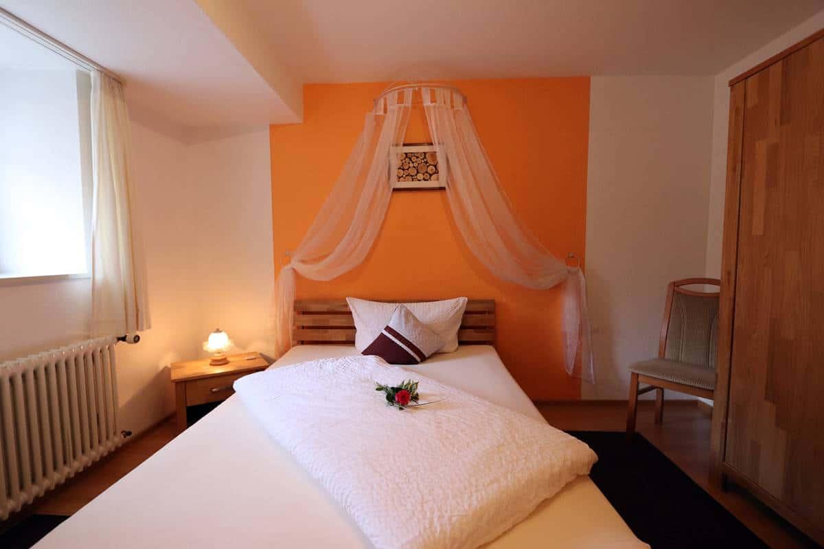 Einzelzimmer Holzwurm mit 1,40 m breitem Bett und Himmel darüber