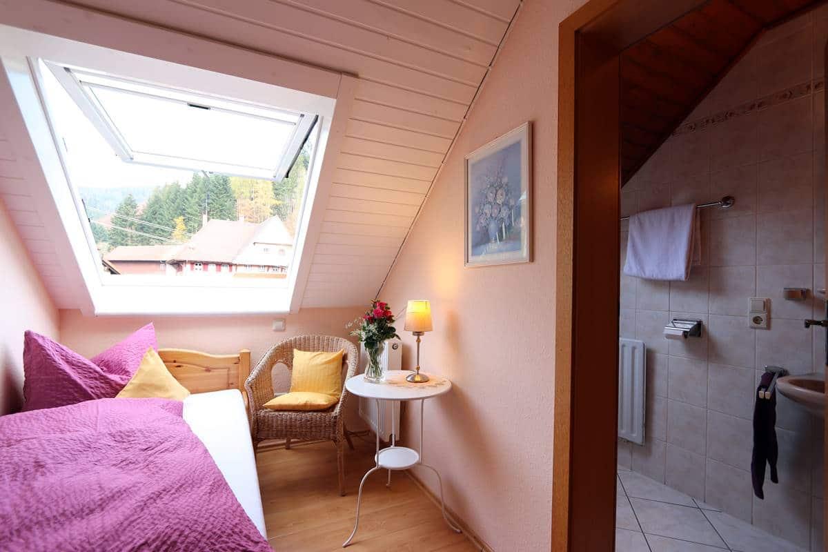 Blick ins Einzelzimmer Sternenblick mit großem Dachfenster überm Bett